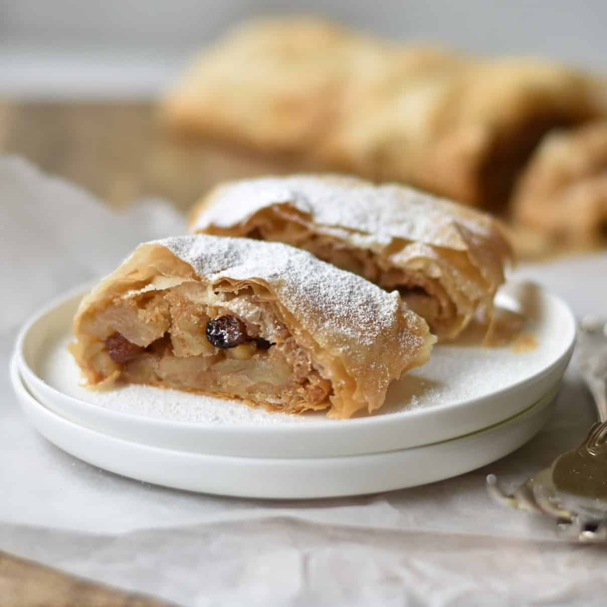 Apple Strudel plated slices dusted with icing sugar.