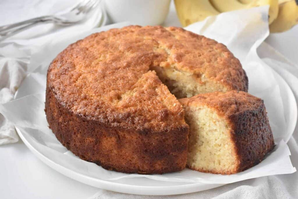 Whole banana cake with one slice cut.