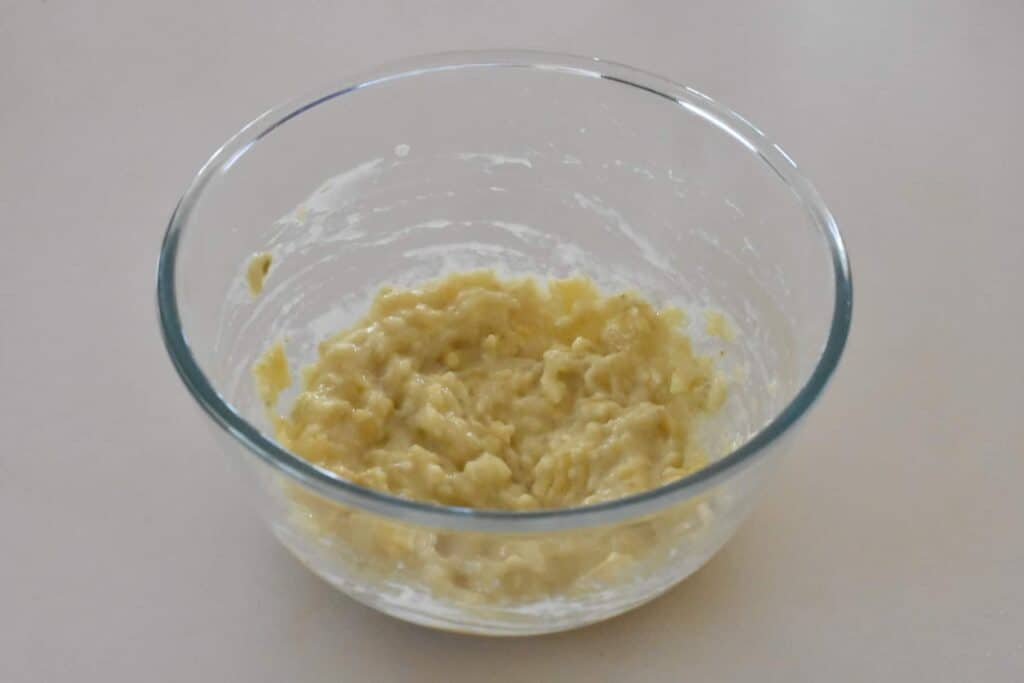Mashed bananas in a large mixing bowl.