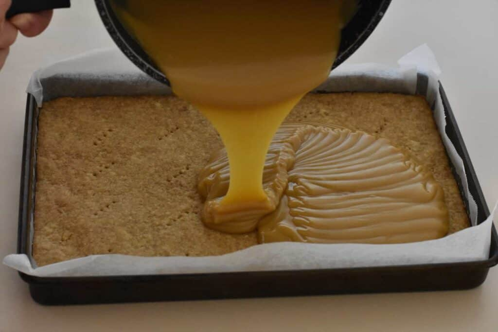 Caramel being poured over the slice base.
