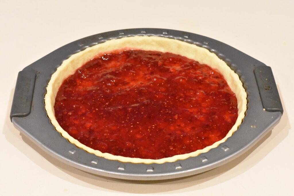 Raspberry filling spread over baked tart shell.
