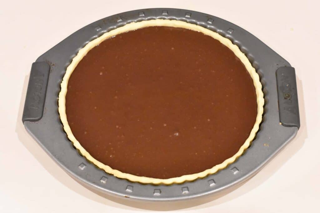 Chocolate filling poured over raspberry layer in tart shell.
