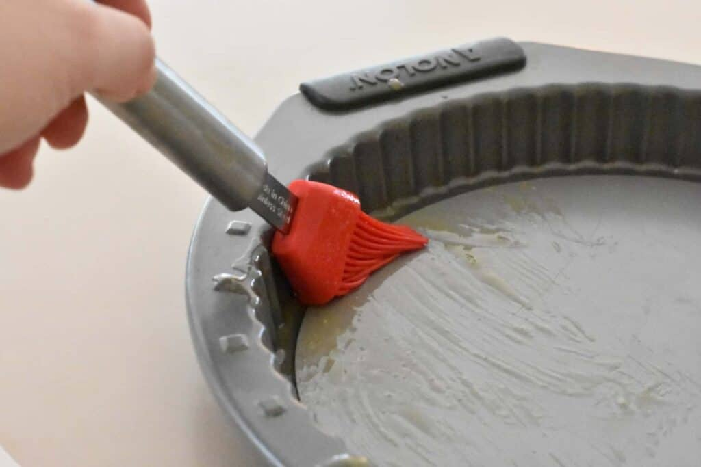 Greasing the tart pan with a silicone brush and melted butter.