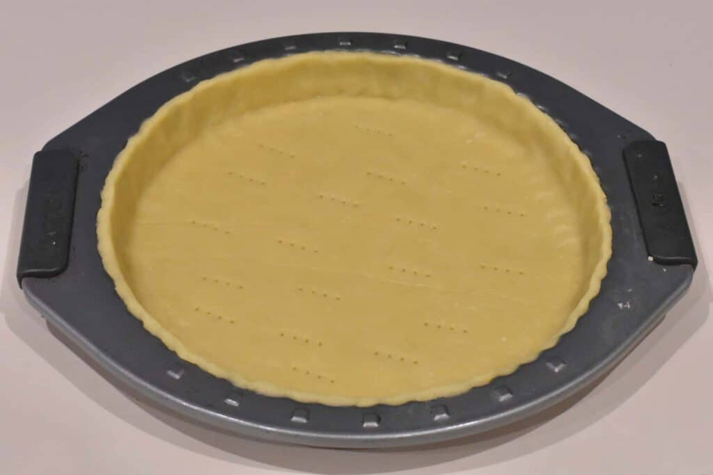 Tart dough pressed into tart tin with edges trimmed.