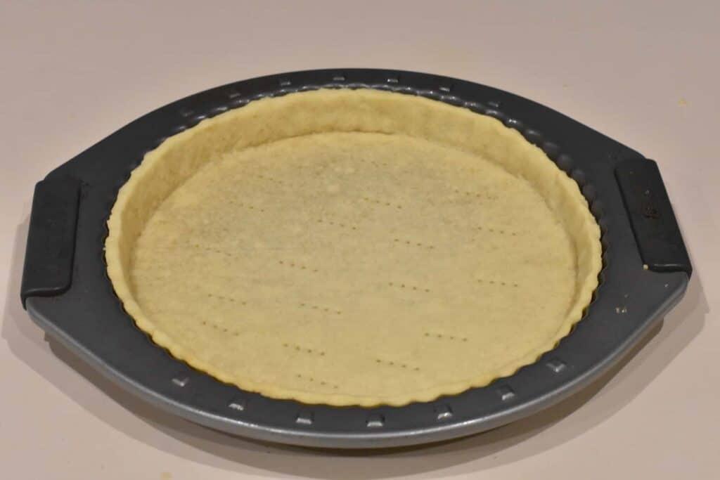 Baked tart shell in tart pan.