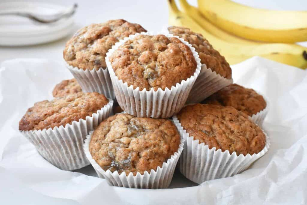 Easy banana muffins stacked on a plate.