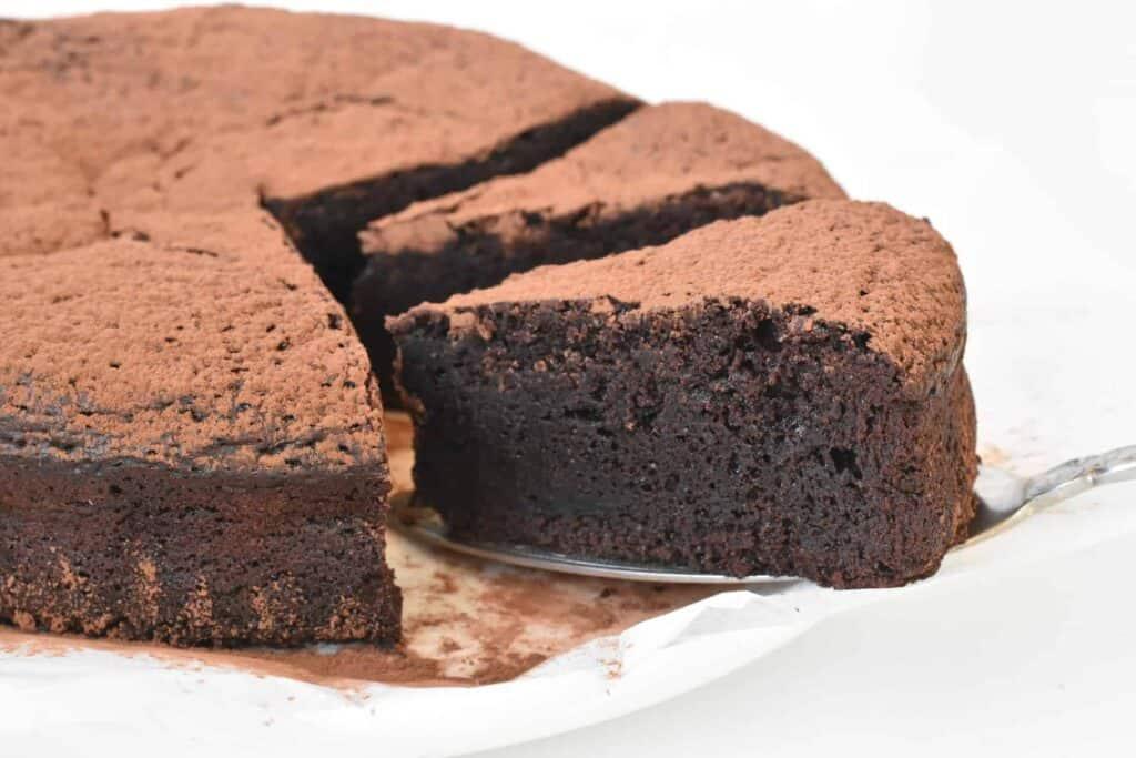 Slice of flourless chocolate cake on cake server.