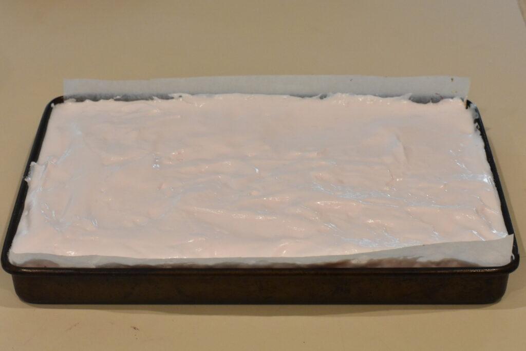 Marshmallow spread over slice in tin.