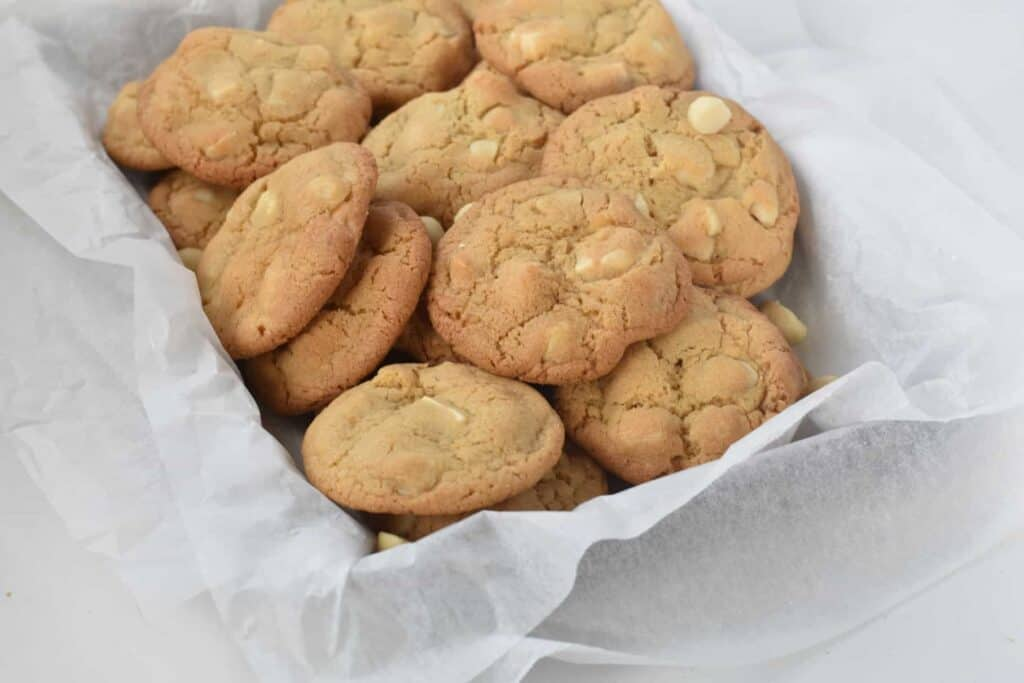 White Chocolate Macadamia Nut cookies stacked up in a tray.