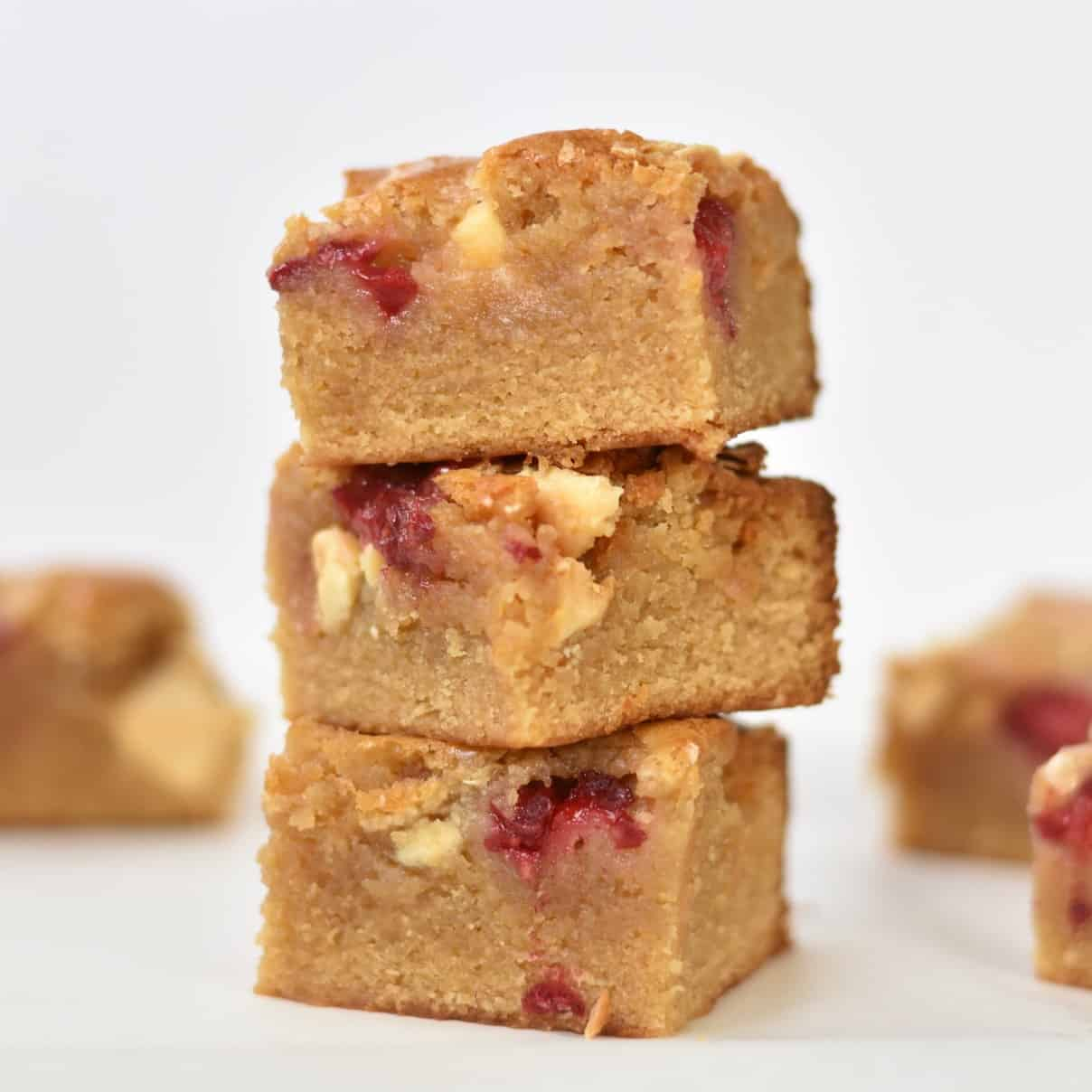 White Chocolate and Raspberry Blondies stacked in a pile.
