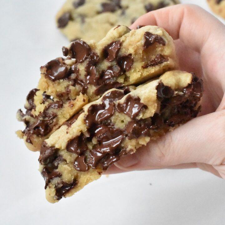 Chocolate chip cookie broken in half while warm.