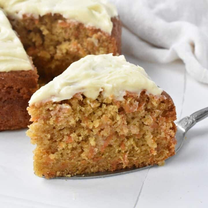 Slice of carrot cake with cream cheese frosting on cake server.