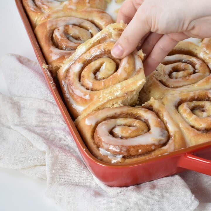Cinnamon Roll being taken from the tray.