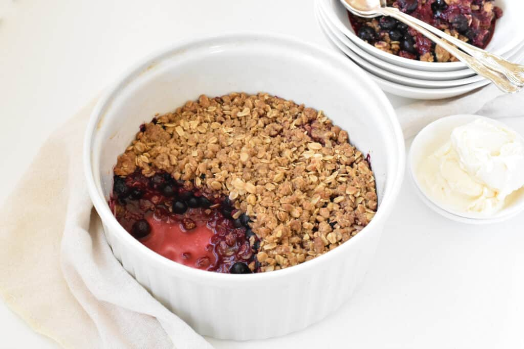 Mixed Berry Crumble being served with ice cream.