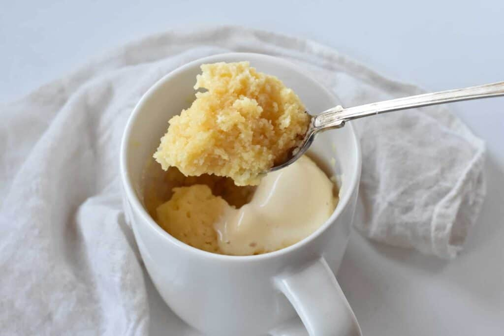 Two ingredient mug cake with spoon and icecream.