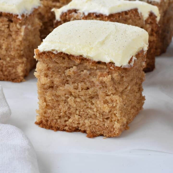 Square of spice cake with frosting on baking paper.