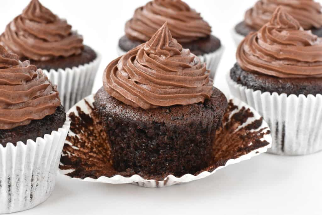Unwrapped chocolate cupcake decorated with swirl of buttercream.