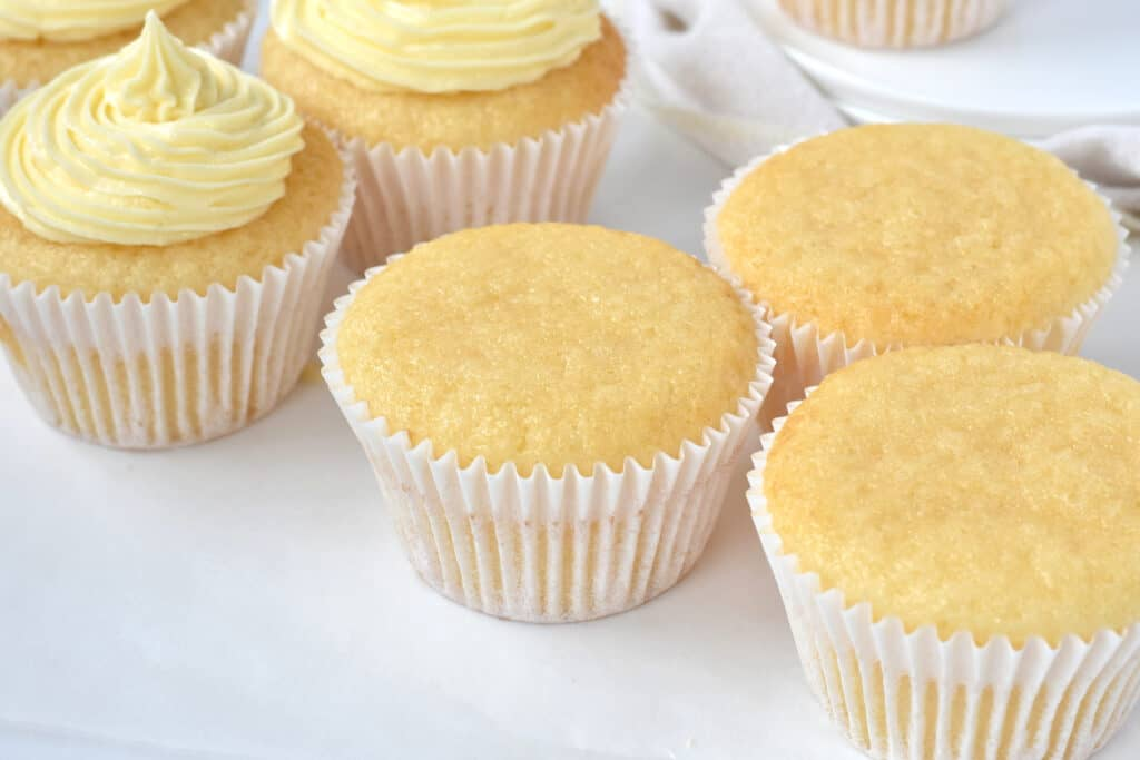 Vanilla cupcakes without frosting on baking paper.