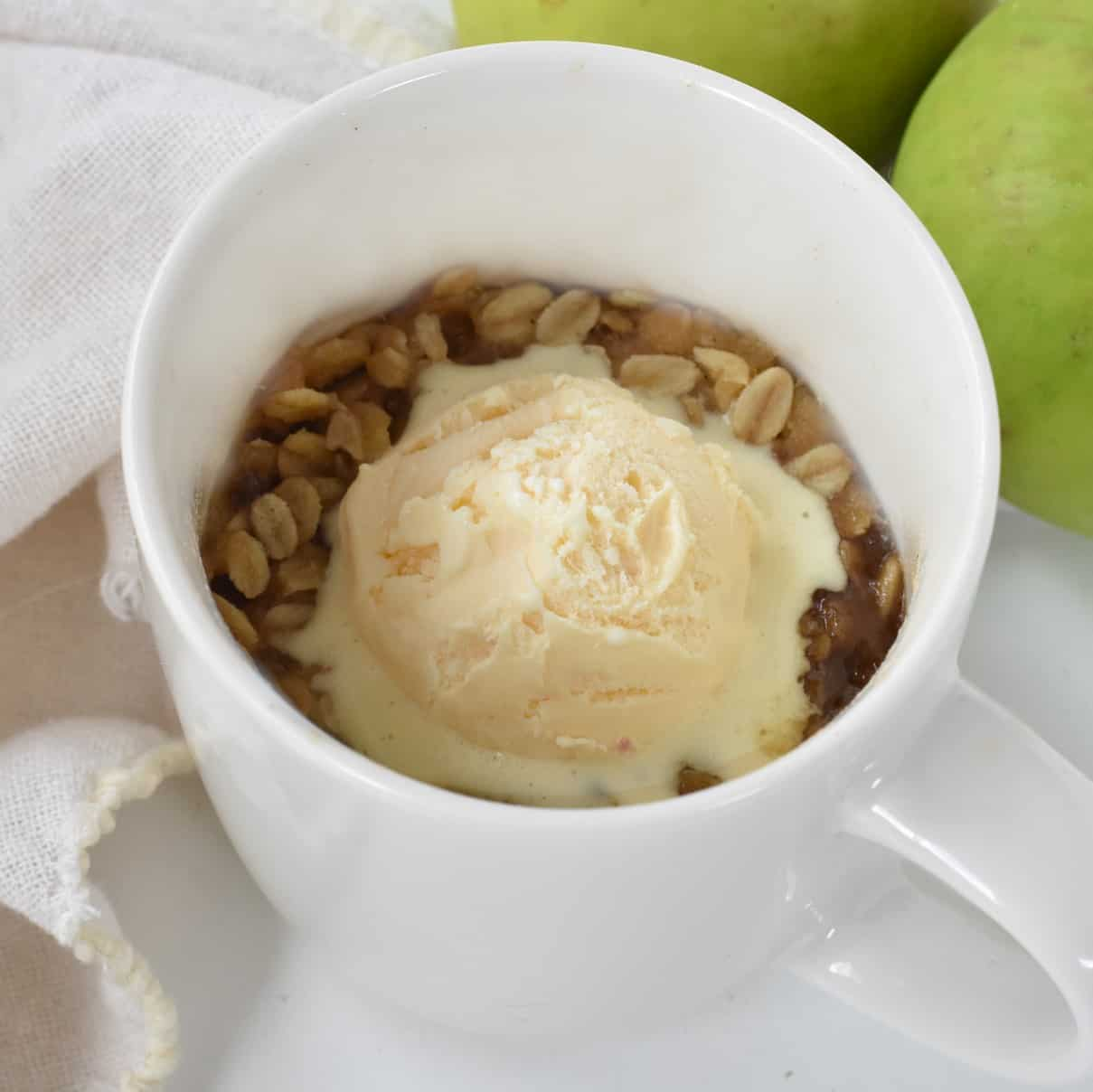 Apple crisp in mug with ice cream.
