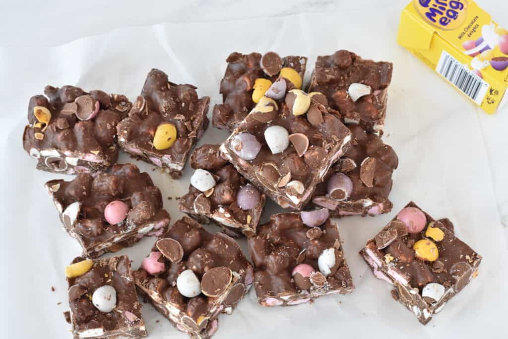 Squares of rocky road stacked on baking paper.